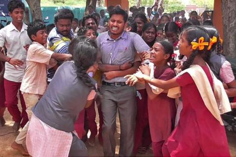 young man who was wearing a simple grey shirt and grey pants is surrounded by students-all of them crying, hanging on to him, holding him back. G Bhagawan, the beloved English teacher